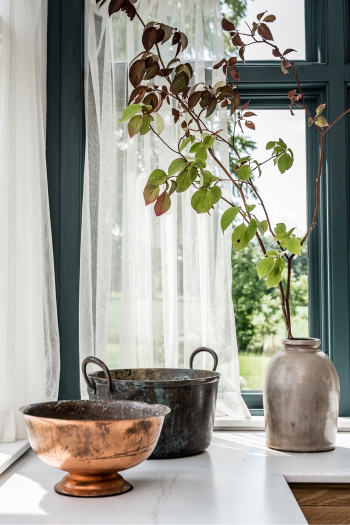 Pots on white counter with window in background